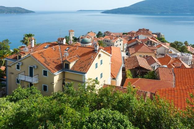 Letni widok na domy z czerwonym dachem i zatoką kotorską z zamku forte mare (herceg novi, czarnogóra)