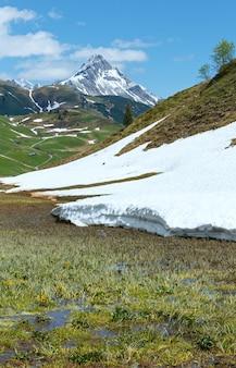 Letni widok na górę biberkopf i łąkę topniejącego śniegu (warth, vorarlberg, austria).