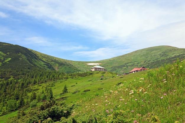 Letni widok na góry z kwiatami i śniegiem na zboczu góry (z pogodą i budynkami stacji biologicznych na grzbiecie czarnogóry, karpaty, ukraina)