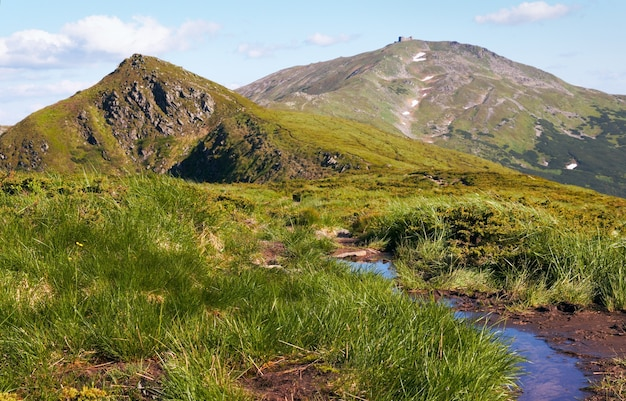 Letni widok na góry z małą kałużą na ścieżce (z ruinami obserwatorium na grzebieniu czarnogóry, ukraina)