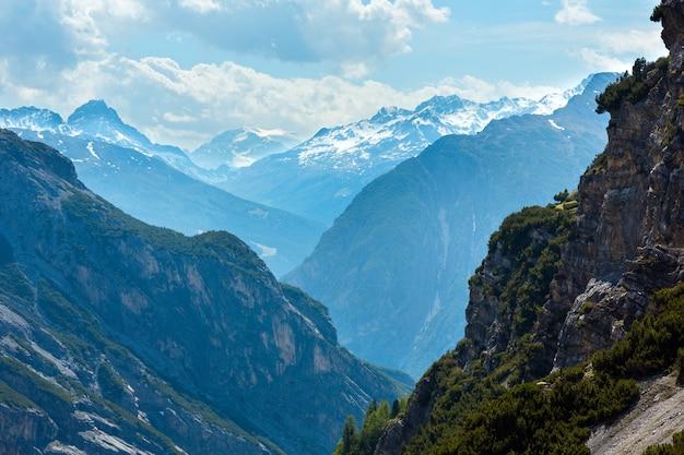 Letni widok na góry z przełęczy stelvio ze śniegiem na szczycie i jodłami na zboczu (włochy)
