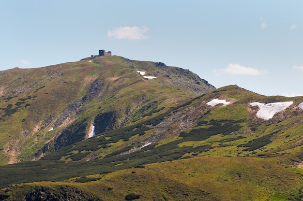 Letni widok na góry ze śniegiem na zboczu góry (z ruinami obserwatorium na grzebieniu czarnogóry, ukraina)