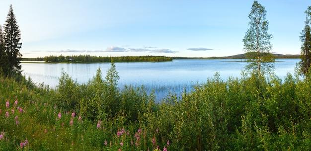 Letni widok na jezioro z różowymi kwiatami z przodu