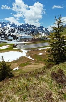 Letni widok na małe jezioro kalbelesee i łąkę topniejącego śniegu (warth, vorarlberg, austria).