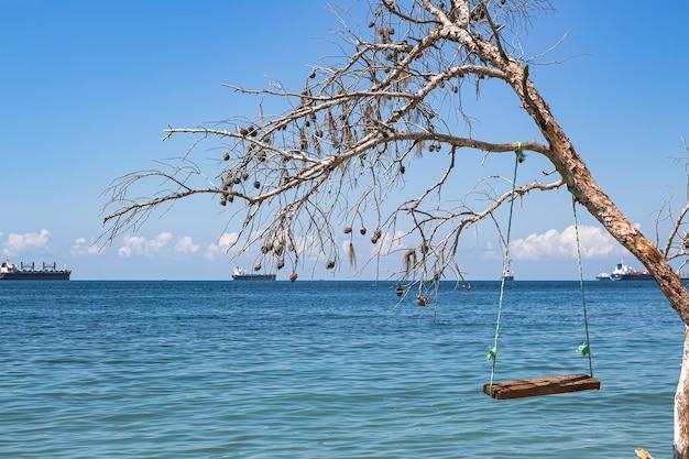 Letni widok na morze, huśtawki na zwalonym drzewie i statki towarowe. domowe huśtawki morskie na dzikiej plaży zabawiają turystów.