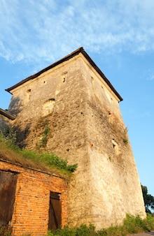 Letni widok na wieżę zamku svirzh w ostatnich wieczornych żółtych promieniach słońca (obwód lwowski, ukraina. zbudowany w xv-xvii wieku.)