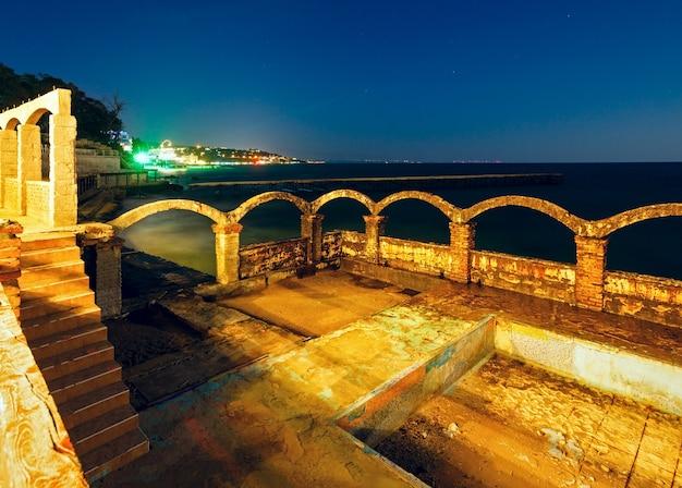 Letni widok na wybrzeże w nocy z ruinami i miastem warna (morze czarne, bułgaria).