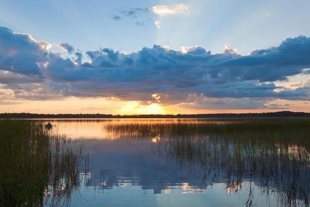Letni widok na zachód słońca nad jeziorem z odbiciami chmur w powierzchni wody i łodzią z rybakiem
