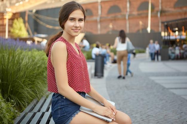 Letni widok na zewnątrz pięknej pozytywnej młodej kobiety w przerywanej czerwonej bluzce i dżinsach za pomocą przenośnego urządzenia elektronicznego w parku, patrząc i uśmiechając się. nowoczesna technologia i komunikacja