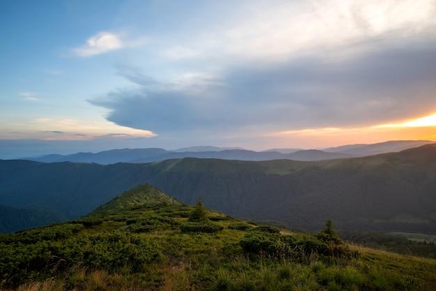 Letni wieczór górski krajobraz z trawiastymi wzgórzami i odległymi szczytami o kolorowy zachód słońca.
