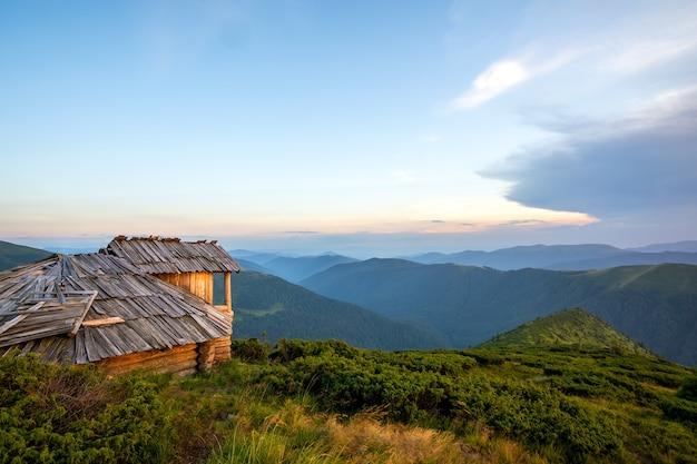 Letni wieczór górski krajobraz ze starym opuszczonym schroniskiem turystycznym na trawiastych wzgórzach i odległych szczytach o kolorowym zachodzie słońca.
