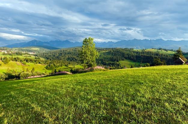 Letni wieczór na przedmieściach górskiej miejscowości z pasmem tatr