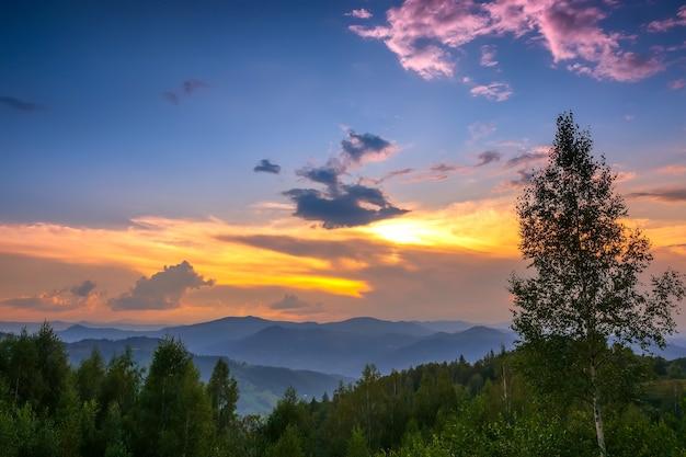 Letni wieczór w niskich zalesionych górach. zachód słońca cieszy się wieloma kolorami
