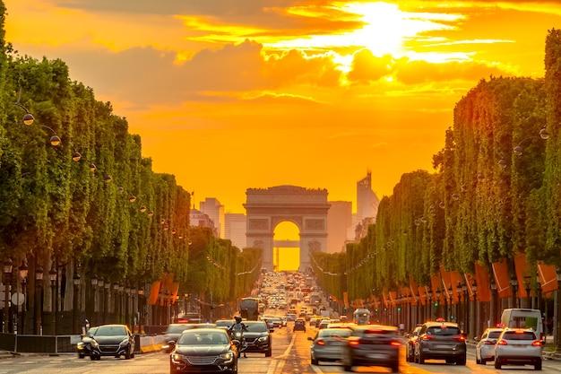 Letni wieczór w paryżu z ruchem ulicznym i łukiem triumfalnym w złotym zachodzie słońca
