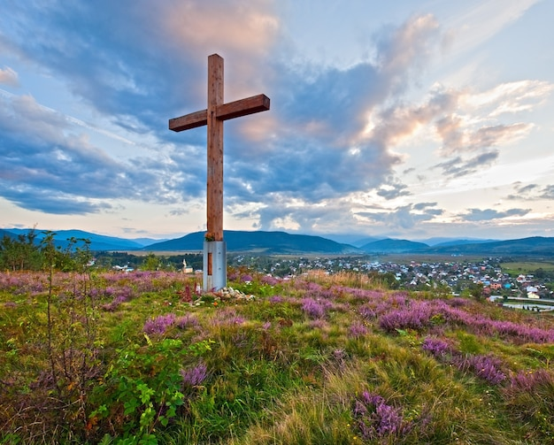 Letni wieczór wiejski widok na przedgórze z kwiatami wrzosu i drewnianym krzyżem (obwód lwowski, ukraina).