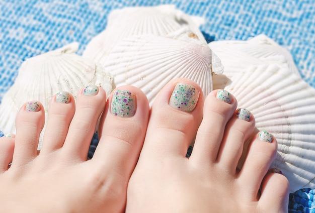 Letni wielokolorowy pedicure na kobiecych stopach.
