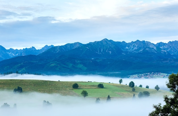 Letni wschód słońca obrzeża górskiej wioski z mgłą i pasmem tatrzańskim (gliczarów górny, polska)