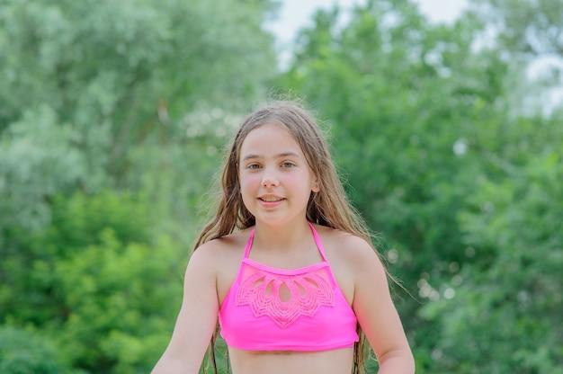 Letni wypoczynek na świeżym powietrzu nad rzeką. zrelaksować się. dziewczynka 9 lat odpoczywa w lecie.