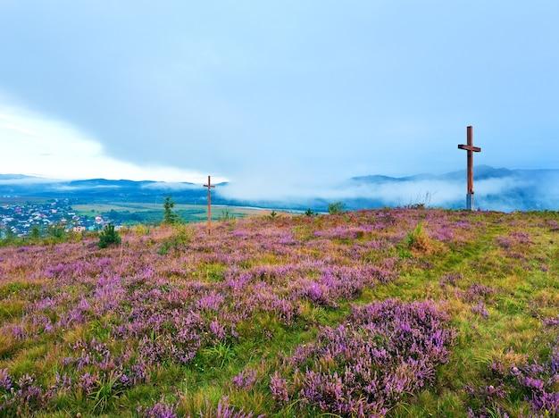 Letni wzgórze kwiat wrzosu, mglisty poranek za widok kraju i drewniane krzyże (obwód lwowski, ukraina).