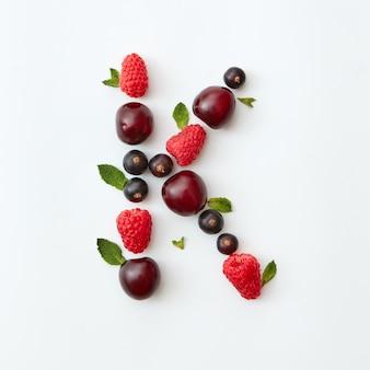 Letni wzór litery k alfabetu angielskiego z naturalnych dojrzałych jagód - czarna porzeczka, wiśnie