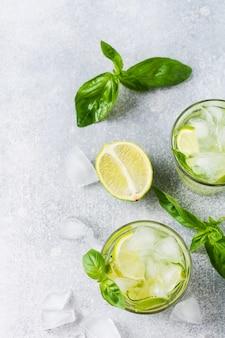 Letnia domowa lemoniada z limonki, cytryny, ogórka i bazylii z lodem w szkle na starym betonie.