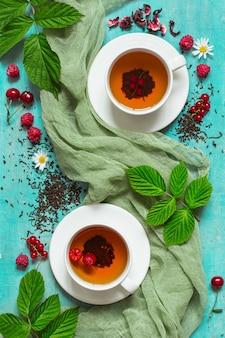 Letnia herbata z jagodami w białych filiżankach.