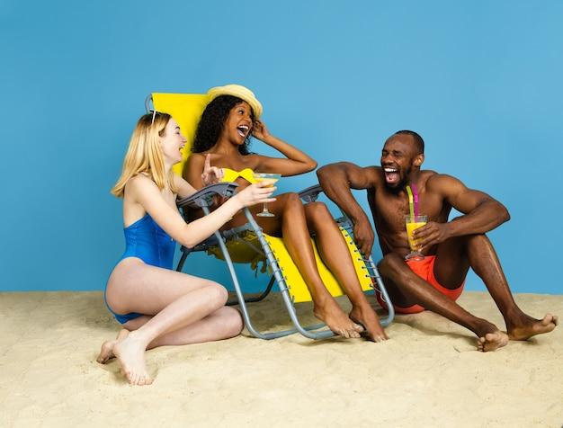 Letnia historia. szczęśliwi młodzi przyjaciele, odpoczynek i zabawa na niebieskim tle studia. pojęcie ludzkich emocji, wyrazu twarzy, wakacji lub weekendu. chill, lato, morze, ocean.