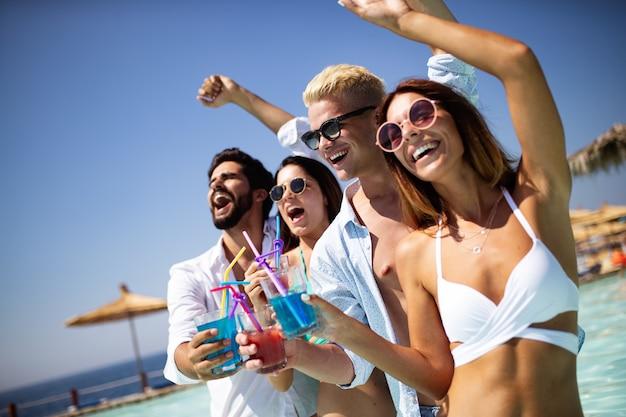 Letnia impreza. grupa przyjaciół na plaży pije koktajle i dobrze się bawi