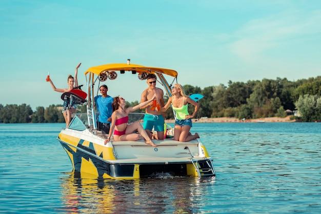 Letnia impreza. szczęśliwi młodzi ludzie świętujący przyjaźń pijący napoje bezalkoholowe na pokładzie łodzi rekreacyjnej