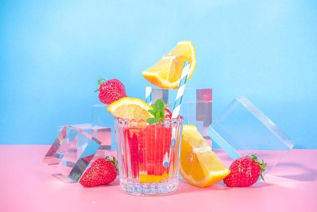 Letnia jasna lemoniada na kolorowym niebieskim różowym tle ze szklanymi cokołami podium ze świeżymi owocami, miejsce kopiowania