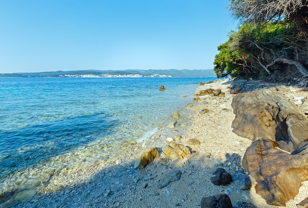 Letnia kamienista plaża i czysta powierzchnia wody adriatyku (chorwacja)