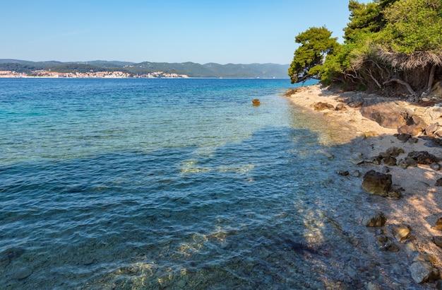 Letnia kamienista plaża z czystą lazurową powierzchnią wody adriatyku (chorwacja) i sosną na brzegu