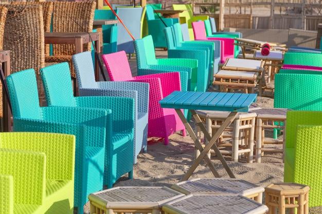 Letnia kawiarnia na tarasie, kolorowe wielobarwne krzesła i stoły na zewnątrz.