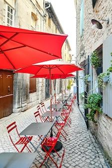 Letnia kawiarnia uliczna z czerwonymi parasolami i krzesłami. puste szare stoły. na świeżym powietrzu francuska restauracja turystyczna na pięknym starym mieście. francja, europa