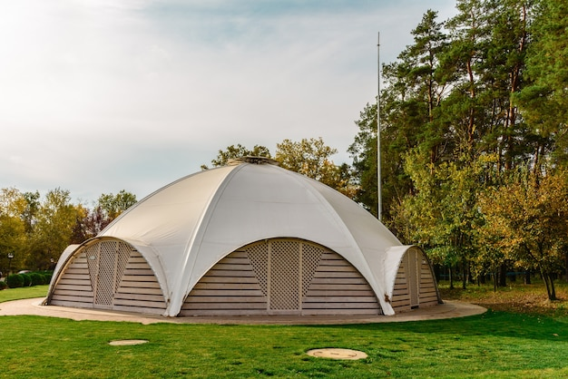 Letnia kawiarnia z namiotem materiałowym na dachu w formie kopuły z drewnianymi drzwiami wejściowymi. miejsce letnich wakacji
