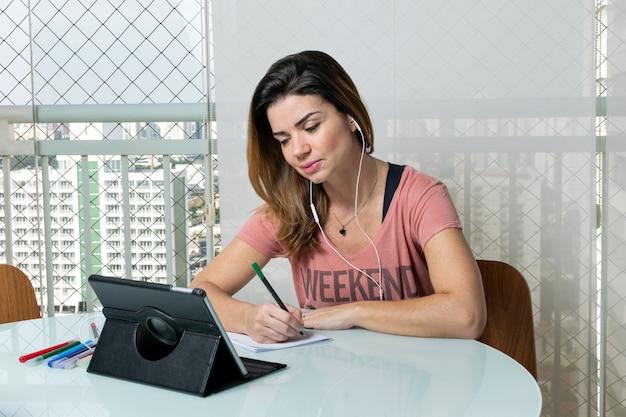 39-letnia kobieta na balkonie mieszkania pracuje, obok grilla i siedzi na kanapie.