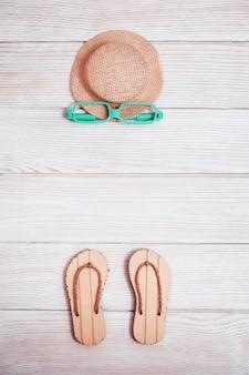 Letnia kompozycja, klapki plażowe, słomkowy żółty kapelusz, okulary przeciwsłoneczne na białym drewnie. w kolorze pastelowym. wakacje nad morzem.