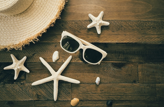 Letnia kompozycja z akcesoriami, rozgwiazdami i muszlami na drewnianym stole