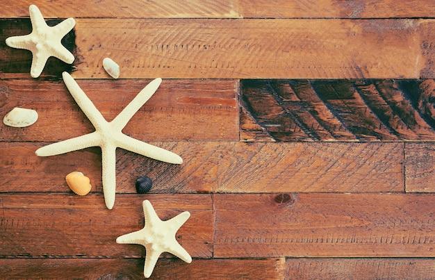 Letnia kompozycja z rozgwiazdy i muszli na drewnianym stole