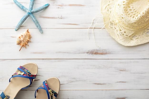 Letnia koncepcja tła kobiece sandały, rozgwiazdy, muszle, słomkowy kapelusz na jasnej drewnianej powierzchni