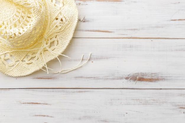 Letnia koncepcja tła, słomkowy kapelusz na jasnej drewnianej powierzchni