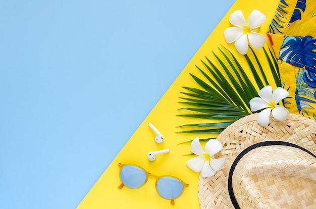 Letnia koncepcja tła z kapeluszem plażowym, okularami przeciwsłonecznymi, liśćmi kokosa, bezprzewodową słuchawką, kwiatami frangipani i kolorową koszulą na żółtym i niebieskim tle