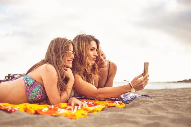 Letnia koncepcja turyści z trzema przyjaciółmi dziewczyny kładą się na plaży, aby się opalać, robiąc zdjęcie selfie za pomocą smartfona - wesoły, szczęśliwi ludzie na wakacjach