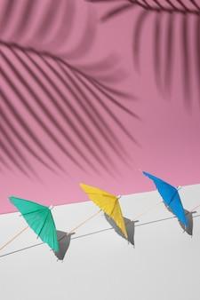 Letnia makieta w białych i różowych pastelowych kolorach. wiele kolorowych parasoli plażowych