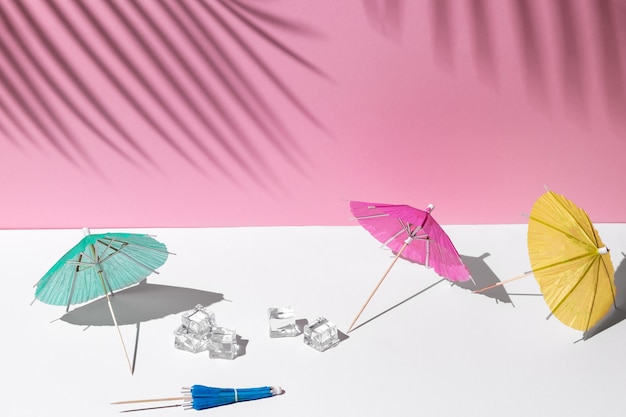 Letnia makieta w białych i różowych pastelowych kolorach. wiele parasoli plażowych lub koktajlowych i kostek lodu w południowym słońcu i twardych cieni z liści palmowych w tle dla przestrzeni kopii copy