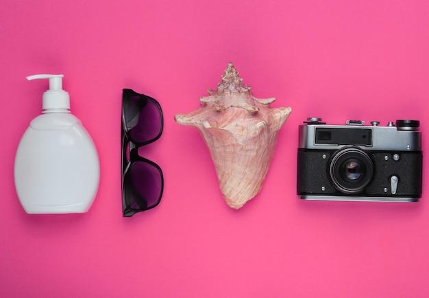 Letnia martwa natura. akcesoria plażowe. aparat retro, butelka z filtrem przeciwsłonecznym, okulary przeciwsłoneczne, muszla na różowo