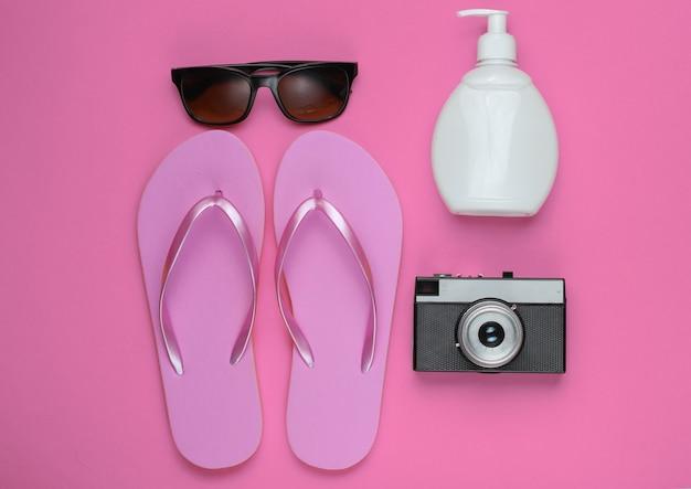 Letnia martwa natura. akcesoria plażowe. modne plażowe różowe klapki, aparat retro, butelka z filtrem przeciwsłonecznym, okulary przeciwsłoneczne na różowym papierze