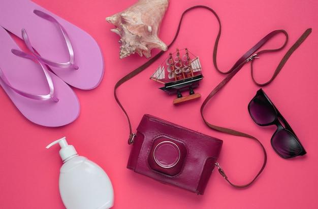 Letnia martwa natura. akcesoria plażowe. modne różowe klapki, aparat retro, butelka z filtrem, okulary przeciwsłoneczne, muszla na różowym papierze