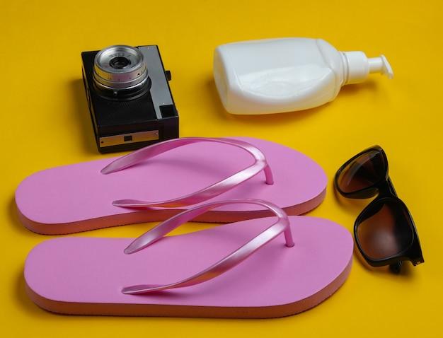 Letnia martwa natura. akcesoria plażowe. modne różowe klapki, retro aparat, butelka z filtrem, okulary przeciwsłoneczne, muszla na żółtym tle papieru.