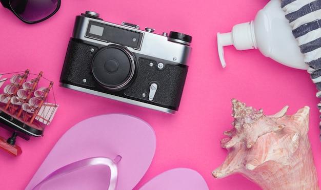 Letnia martwa natura. akcesoria plażowe. modne różowe klapki, torba, aparat retro, butelka z filtrem, okulary przeciwsłoneczne, muszla na różowym papierze